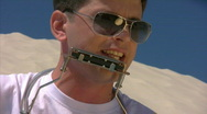 Singing man in sunglasses with harmonica on beach Stock Footage