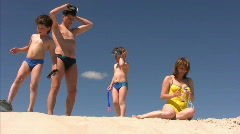 Family with flippers, goggles and pipes on beach Stock Footage
