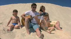 Perheen kitara ja huuliharppu laulaa rannalla Arkistovideo