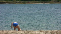 Boy in beach throwing stone in river Stock Footage