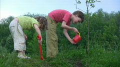 Boy watering young plant, girl digging hole Stock Footage