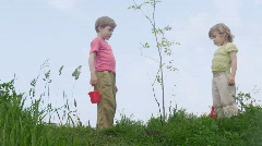 Boy with bucket and girl with shovel takls about young plant Stock Footage