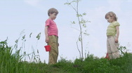 Stock Video Footage of boy with bucket and girl with shovel takls about young plant