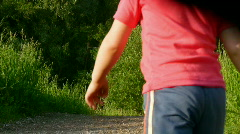 Boy and girl holds doll and walks in park Stock Footage