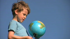 Boy stands and looks at terrestrial globe Stock Footage