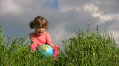 Girl with terrestrial globe sits on grass against sky Stock Footage