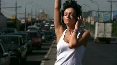 Dancing girl in headphones on highway middle Stock Footage