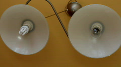 Old light bulb and new fluorescent light bulb Stock Footage