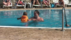 Kid plays with dad in the pool - stock footage