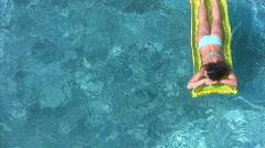 Woman in bikini on inflatable mattress in water pool Stock Footage
