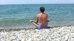 Man sitting on beach in pose of lotus and looks at sea Stock Footage