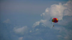 Parasailing two humans on parachute flying in sky Stock Footage
