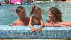 Family talks in swimmig pool outdoor Stock Footage