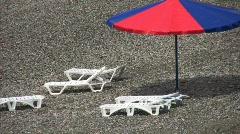 Beach umbrella and beach beds on pebble coast Stock Footage