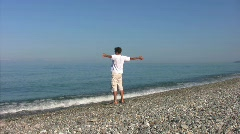 Man warming up on beach against sea Stock Footage