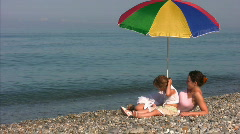 Mother with daughter under umbrella on shore Stock Footage