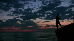 Man stands on rock and throws pebbles into sea under sunset sky Stock Footage