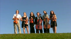 Six musicians with bow instruments stands on hill Stock Footage