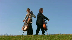 Man and woman plays violoncellos on hill Stock Footage