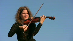 young woman plays violin against blue sky - stock footage