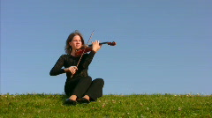 woman sits on meadow and plays violin - stock footage