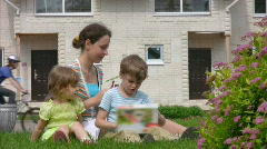 Mother and daughter and son opens box with model toy house Stock Footage