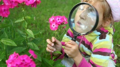 Girl observe pink flowers through magnifying glass in summer Stock Footage