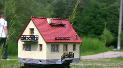 Toy house standing outdoor, defocused people in background Stock Footage