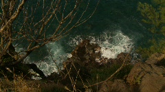 Rocky shoreline and surf straight down, vertigo inducing Stock Footage