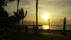 Sunset, silhoutted people at the beach resort Stock Footage