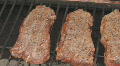 Steaks cooking on charcoal grill pan left to right HD Footage