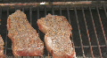 Steaks cooking on charcoal grill pan right to left HD Footage