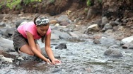 Stock Video Footage of Woman drinking clean pure water from stream during hiking