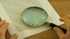 Male picking up Magnifying Glass to look at small print in contract Stock Footage