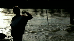 Boy throwing rocks into water at Sunset Stock Footage