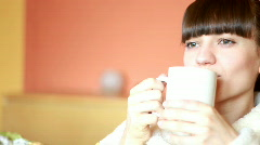 Young woman in bahtrobe drinking tea Stock Footage