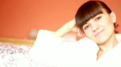 Young Woman in a bathrobe sitting on the sofa and relax, dolly shot Stock Footage