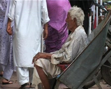 Old Beggar in Wheel barrow outside Market in Karachi, Pakistan Stock Footage
