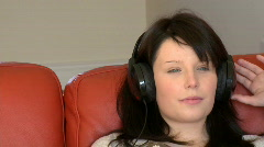 Attractive woman listening music sitting on bed - stock footage