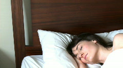 Tired woman relaxing in a bed Stock Footage