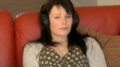 Relaxed woman sitting on sofa and listening music - stock footage
