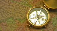 Old brass compass over antique map Stock Footage