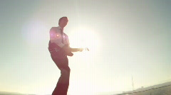 Man plays the guitar on the background of the sun Stock Footage