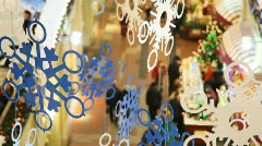 Paper snowflakes on cords, against shopping centre pavilions Stock Footage