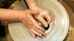 Hands mould pot rotating on potter's wheel and moisten with its sponge Stock Footage
