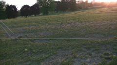 Swinging at driving range in setting sun Stock Footage