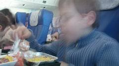 Serious boy eats in plane salon Stock Footage