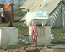 Women Fill Drinking Water from a Tank in  Refugee Camp Stock Footage
