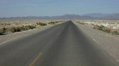POV of car driving down desert road Stock Footage