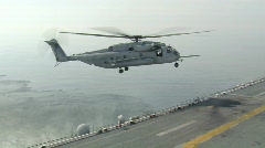 Helicopter Hovers and Lands on Aircraft Carrier (HD) Stock Footage